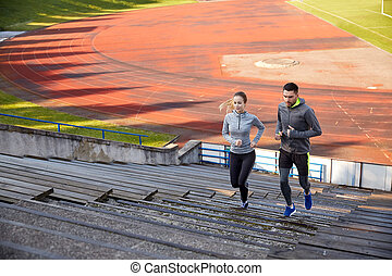 happy couple running upstairs on stadium - fitness, sport,...