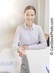 smiling businesswoman shaking hand in office - business and...