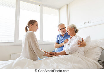 happy family visiting senior woman at hospital - medicine,...