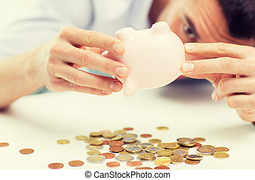 close up of man pouring coins from piggy bank - business,...