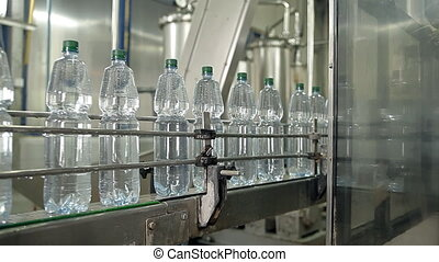 The machine is pouring mineral water into bottles - A large...