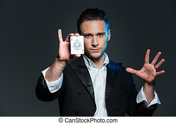 Confident young man magician showing ace card over grey...