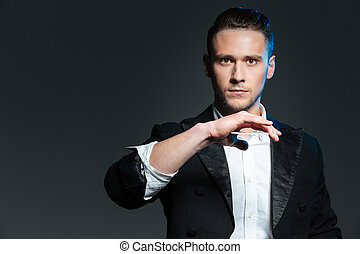 Handsome young man magician showing tricks with playing...