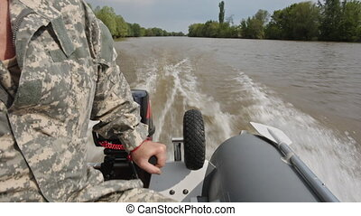 Man drives a motor boat quickly rushing river