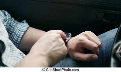 Man hands using smart watch sitting in car - Man hands using...