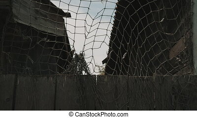 Old fishing net weighs on the fence around the house and...