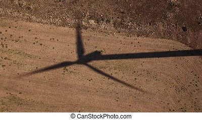 Top view of windmill shadow over cultivated land - Aerial...