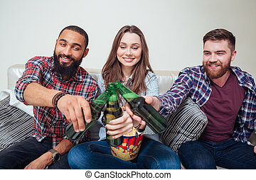 Friends drinking beer at home together