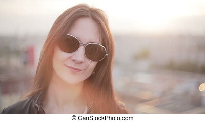Girl in sunglasses standing on the roof at sunset - Girl in...