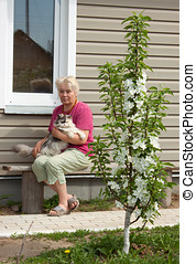 Woman on a summer residence with a cat on hands - Woman sits...