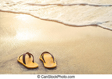 Yellow flip flop on the beach with bright light of sunset in...