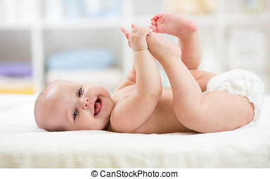 Funny little baby wearing a diaper playing on bed in nursery room. Happy child after bath or shower. Infant kid diaper change and skin care. Smiling kid playing with his feet.