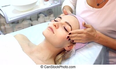 Beauty woman having cosmetic massage, facial treatment,...