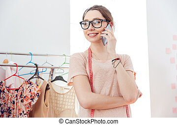 Smiling woman fashion designer in glasses standing and using...