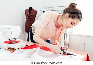 Focused woman fashion designer cutting white fabric in...