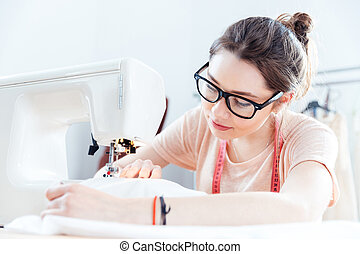 Serious woman seamstress at work with cloth fabric - Serious...