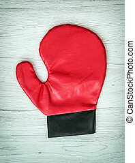 Red boxing glove on the wooden background, leisure activity...