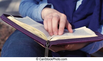 Close-up of woman's hands while reading the Bible outside.
