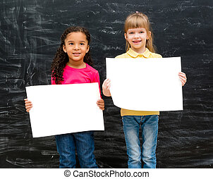 two pretty little girls with blank paper in hands and chalky...