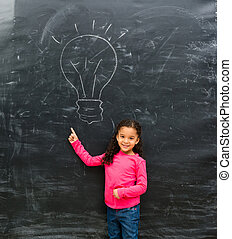 smiling little girl pointing at drawn on the blackboard lamp...