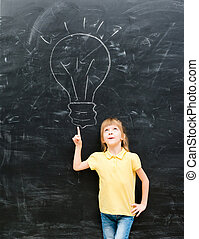 cute little girl pointing on a drawn lamp on chalky...