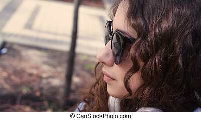 beautiful young woman in sunglasses looking ahead.