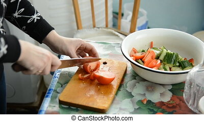 Woman hands slicing tomato in a rustic kitchen