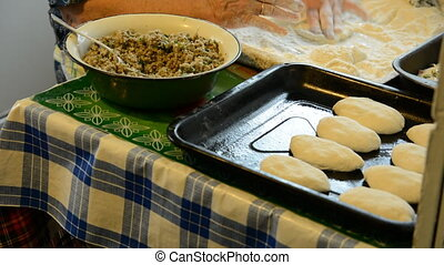 Cooking meat pies. Old woman unrolls dough and fill it with...