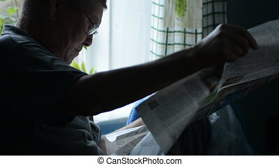 Senior man with reading newspaper