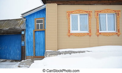 Old wooden house with carved frames in the winter. Home and...