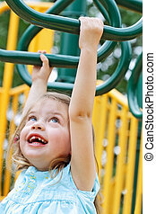 Child Crossing Monkey Bars - Happy little girl crosses...