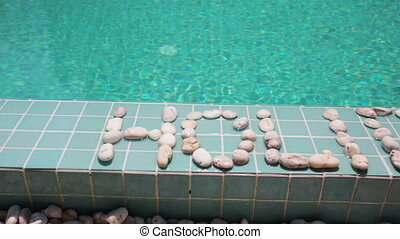 The inscription holiday is laid out by pebble on a pool side...