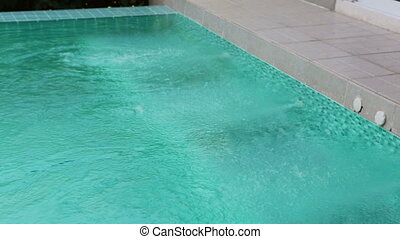 bubbles from jacuzzi streams in the pool ,