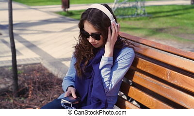 young woman in sunglasses listening to music with headphones...