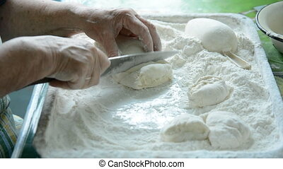 Old women cuts the dough for making pasta.