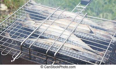 Fish fried on a grill with smoke