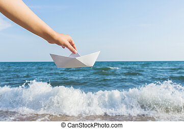 Female hand holding paper boat on the sea background