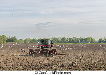 Red tractor ploughing on the arable land - A red tractor...