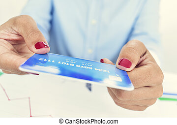 young woman with a credit card in her hands - closeup of a...