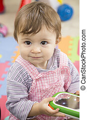 Portrait of cute baby girl holding toy - Portrait of...