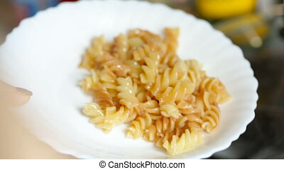 Ready macaroni dish is shifted to a white plate. Video full...
