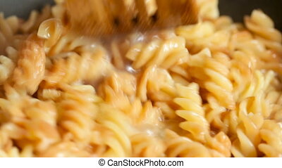 Dish with macaroni in a pan is stirred a wooden shovel Video...