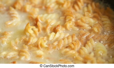 Dish with macaroni in a pan boils. Close up video full hd.