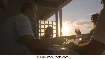People toasting during dinner on the balcony