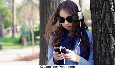 beautiful young woman in sunglasses listening to music with headphones in the park