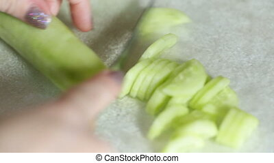 Female hands cut a cucumber on small pieces.
