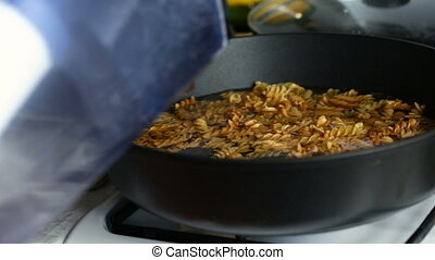 Water is added to a frying pan with fried macaroni. Video...