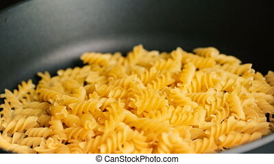 Macaroni adds to a frying pan then mixes a wooden shovel...