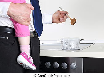 Businessman cooking with Baby on arm - A Businessman cooking...