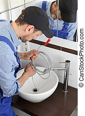 Plumber cleaning a pipe drain with a Spiral